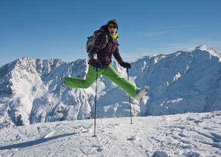 woman in ski cloths jumping over the snowy mountains, austria photo