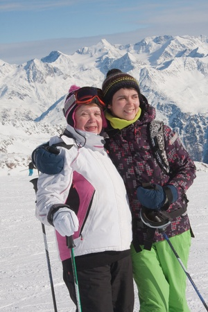 Alpine skiers ( mother and daughter) mountains in the background photo