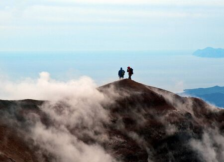 sulfide: The Tourists look at the Pacific ocean with of the volcano. Kamchatka.