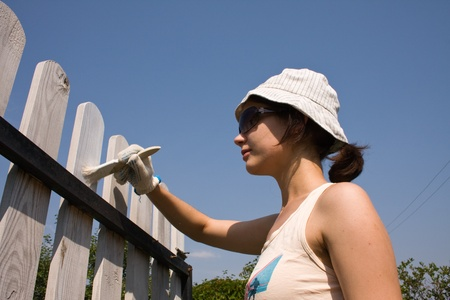 Beautiful girl colours the wooden fence Stock Photo