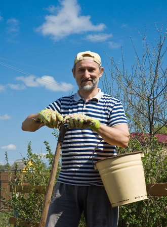 A man with a rake and a bucket in the garden photo