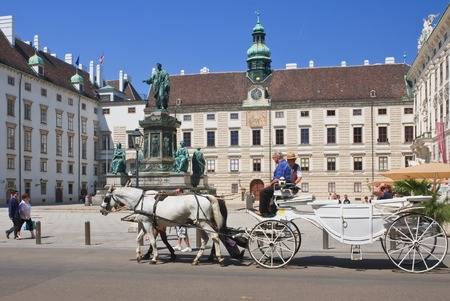 franz: Tourists riding horse-drawn carriage in front of the residence of the Hofburg in Vienna, Austria