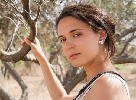 Portrait of a beautiful young brunette in the background of olive groves