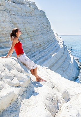scala: A girl sits on a slope of white cliff called Scala dei Turchi in Sicily, near Agrigento. Italy