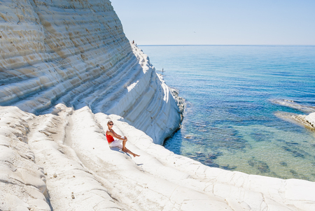 A girl sits on a slope of white cliff called Scala dei Turchi in Sicily, near Agrigento. Italy