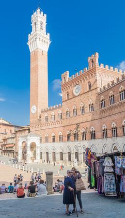 Tourists do selfi. Piazza del Campo with Palazzo Pubblico in Siena, Italy Editorial