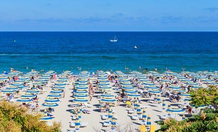 De Zwarte Zee kust, blauw helder water, strand met zand, parasols en ligbedden. Albena, Bulgarije