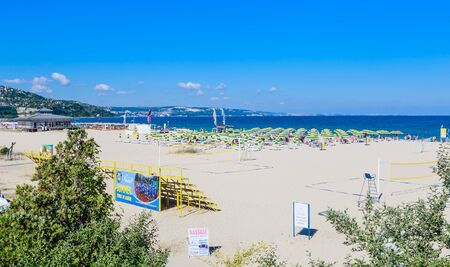 The Black Sea shore, blue clear water, beach with sand, umbrellas and sunbeds. Albena, Bulgaria