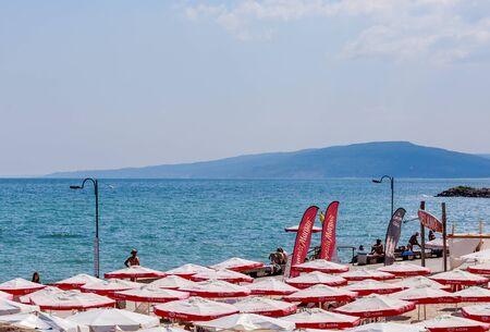 The Balchik seaside, beach with sands, sun umbrellas and blue water.