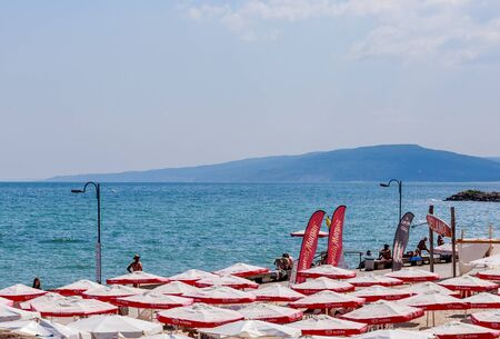 balchik: The Balchik seaside, beach with sands, sun umbrellas and blue water.