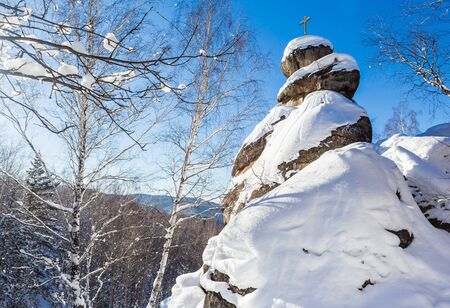snowdrifts: A rock with an Orthodox cross. Mountain Church. Resort Belokurikha, Altai, Russia Stock Photo