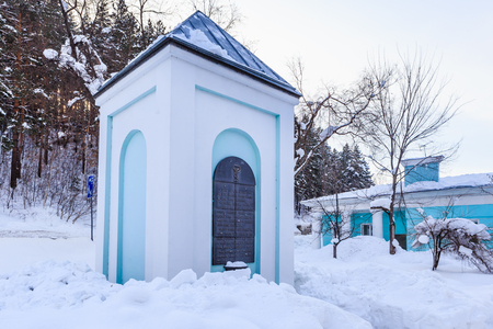 Memorial sign in the form of a small chapel Serpentine well and the buildings of the former hydropathic institution.  Resort Belokurikha. Altai, Russia