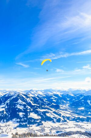 Paragliding over the mountains in winter. Ski resort  Hopfgarten, Tyrol, Austria