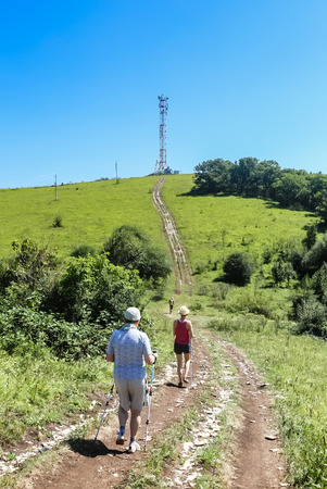 Tourists walk along the road to communications tower on top of a hill