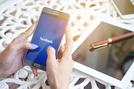 Bangkok, Thailand - February 12,2017:holding a Samsung note5  with social networking service Facebook on the screen. iPhone 6 was created and developed by the Apple inc. Editorial