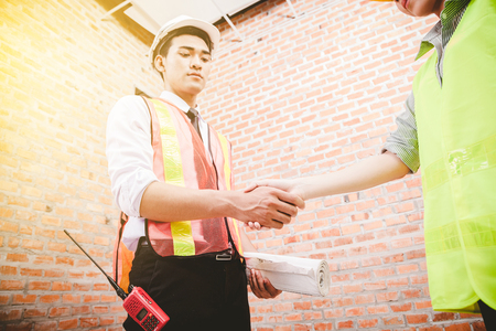 windows: Engineers shaking hands at construction site for architectural project,  Stock Photo