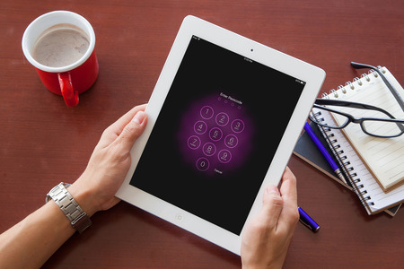 Bangkok, Thailand - June 19,2016 : Apple Ipad2 held in one hand showing its screen with numpad for entering the passcode. Editorial