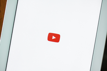 BANGKOK,THAILAND - Mar 11,2016: A loading screen of YouTube app on iPhone and a landing page of YouTube website on iPad. YouTube was founded by Chad Hurley, Steve Chen and Jawed Karim.
