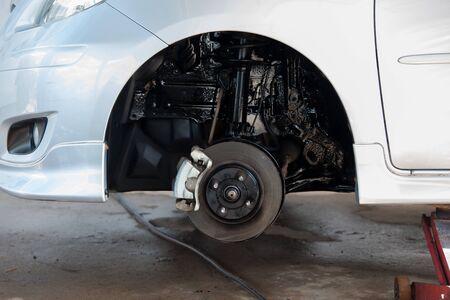 Closeup disc brake of the vehicle for repair, in process of new tire replacement. Car brake repairing in garage
