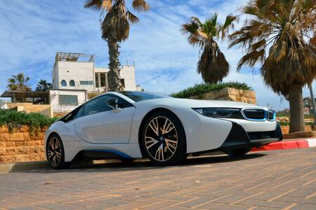 Tel-Aviv, Israel - 15.02.2018: White BMW i8 car parked on the street near white house and palm trees. Luxury hybrid vehicle Redactioneel
