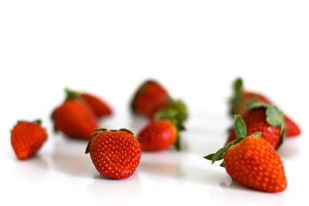 Bright red fresh ripe strawberries berries scattered and isolated on a white background.