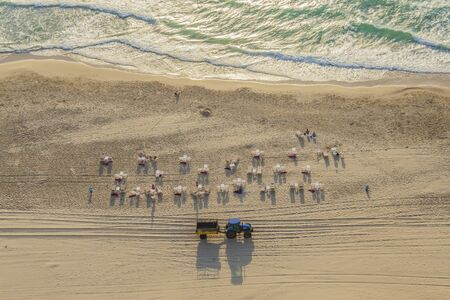 Aerial top view of the Israeli beach on the shores of the calm Mediterranean Sea at sunset. There are few people, red umbrellas are already assembled, a tractor arrives past