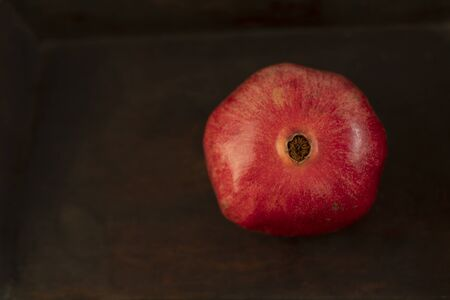 Fresh red pomegranate - whole, on a wooden vintage background, top view