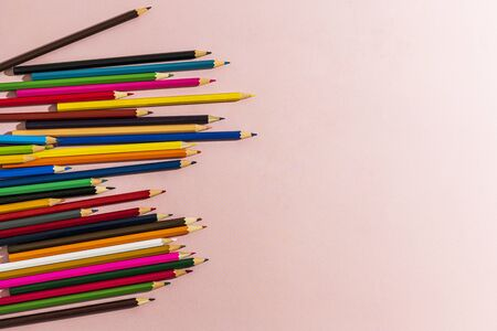 Scattered colored pencils of different lengths on a pink background on the left side, tending to the center. Horizontal view.