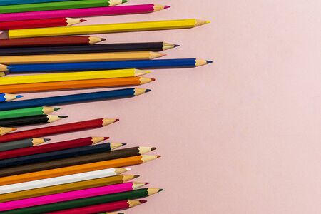 Scattered colored pencils of different lengths on a pink background on the left side, tending to the center. Horizontal close-up. Imagens