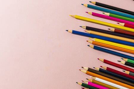 Scattered colored pencils of different lengths on a pink background on the right side, tending to the center. Horizontal close-up.