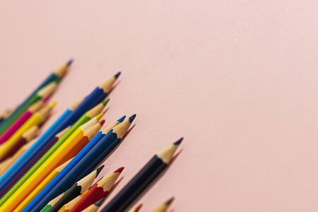 Multi-colored pencils of different lengths on a pink background, located on the left corner, extending into the distance. Horizontal close-up.
