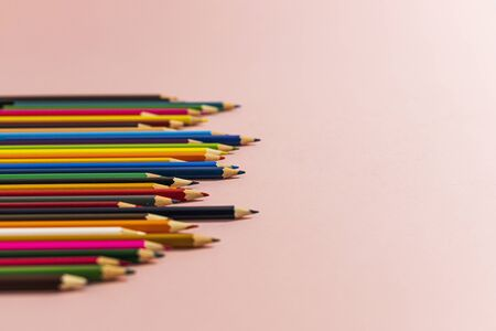 Colored pencils of different lengths are scattered, extending into the distance, on a pink background on the left side, tending to the center. Horizontal side view.