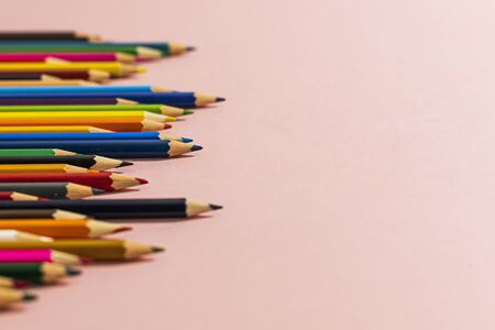 Colored pencils of different lengths are scattered, extending into the distance, on a pink background on the left side, tending to the center. Horizontal close-up.