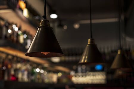 Metallic dark retro chandeliers are suspended from the ceiling. Modern, relevant and at the same time vintage design. Conceptual style. Loft lamps hang in a restaurant or cafe, in a bar or club, in ar