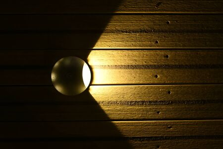 A lit street lamp is inserted or attached to the ground, namely to the wooden deck of the bridge. Street lighting of a modern city. An orangeish light illuminates the wooden floor. On the wooden flooring, holes for nails are visible. Decorative style, architectural idea. Ideal for captions and headings.