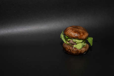 A healthy burger with baked mushrooms instead of bread rolls. Made with fried meat patty, with salad leaves, onions, apples and avocado mayonnaise. Copy space. Horizontal view. Side view. Banque d'images