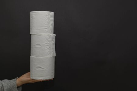 Female hand holds three rolls of toilet paper. Column. The concept of trends, purchases, shortages of goods and panic in global viruses, epidemics, pandemics. If the person is a carrier of a virus or infection, he is recommended to wear a protective mask, otherwise he can infect other people. It is better for a person with a cold, cough, fever, flu to stay at home, isolate himself, go to quarantine. In an epidemic, pandemic, or environmental pollution, it is safer to carry disposable masks, gloves, and an antiseptic, that is, a disinfectant. Hand and face hygiene is important. This is a way to reduce the spread of the virus. Your safety is your health. In the midst of illness, there may be a shortage of this product, a crisis, because people buy everything in a panic. Horizontal view. Dark background. Copy space.