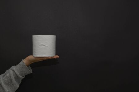 Female hand holds a roll of toilet paper. The concept of trends, purchases, shortages of goods and panic in global viruses, epidemics, pandemics. If the person is a carrier of a virus or infection, he is recommended to wear a protective mask, otherwise he can infect other people. It is better for a person with a cold, cough, fever, flu to stay at home, isolate himself, go to quarantine. In an epidemic, pandemic, or environmental pollution, it is safer to carry disposable masks, gloves, and an antiseptic, that is, a disinfectant. Hand and face hygiene is important. This is a way to reduce the spread of the virus. Your safety is your health. In the midst of illness, there may be a shortage of this product, a crisis, because people buy everything in a panic. Horizontal view. Dark background. Copy space.