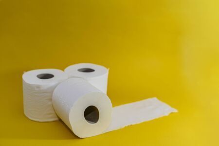 Close-up. Three rolls of toilet paper are stacked on a beautiful bright yellow background. One roll lies next untwisted. Essential goods. Purchasing power. The concept of trends, purchases, shortages of goods and panic in global viruses, epidemics, pandemics. If the person is a carrier of a virus or infection, he is recommended to wear a protective mask, otherwise he can infect other people. It is better for a person with a cold, cough, fever, flu to stay at home, isolate himself, go to quarantine. In an epidemic, pandemic, or environmental pollution, it is safer to carry disposable masks, gloves, and an antiseptic, that is, a disinfectant. Hand and face hygiene is important. This is a way to reduce the spread of the virus. Your safety is your health. In the midst of illness, there may be a shortage of goods, a crisis, because people are in a panic buying everything. Horizontal view. Bright background. Copy space.