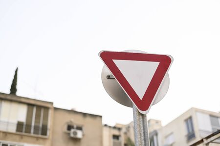 Cars, roads, tracks, highways. Triangular road sign. Give Way. The sign is located on the street. There is also a sign on the other side of the pillar, but it is not visible. Safety of movement. Restriction of movement. European standard. Close-up. The background is blurred, there are urban residential buildings.