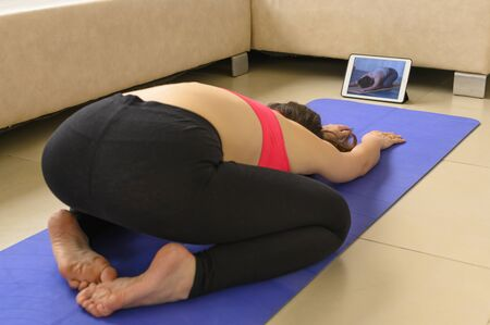 Home view. Classes in the apartment or at home. Girl on a sports mat for yoga classes. She is dressed in a sporty pink bright top and black skinny legends. Hairstyle ponytail. Black dark hair. Athletic brunette girl doing sports exercises. In front of her is a tablet with online courses where you can see the image. She repeats the exercises. The girl's back, her face is not visible. In the background is a light sofa. Topical activities online during viruses and epidemics. Self-discipline, self-control, weight loss, a healthy lifestyle. During epidemics, viruses, and a pandemic, it is recommended that you stay at home, not go out and reduce contact with friends and other people. Perhaps the girl works, she is a coach, a sports teacher, a yoga teacher. Videoconference, video broadcasting, or gives advice, sports, study. The concept of online life, online orders, online shopping, online study, training. Perhaps she is in quarantine or self-isolation, alone. Copy space. Horizontal view. At home. Living room. Stock fotó