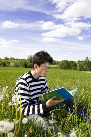 Reading boy sit in a field with a book Stock Photo