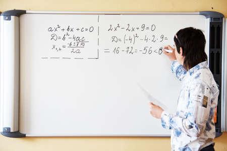 maestra ense�ando: Joven maestro de ense�anza algerbra ecuaci�n cuadr�tica y escribe en una pizarra