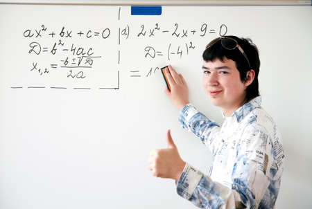 Young teacher teaching algerbra  and writes quadratic equation on a whiteboard Stock Photo