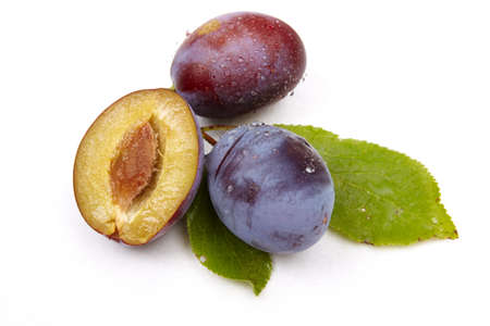 Whole plum and halves isolated on the white background photo
