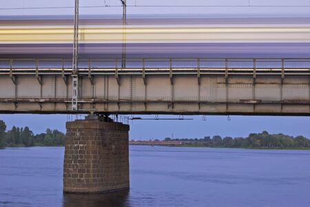 river bank: The morning express train on the bridge across Daugava river.