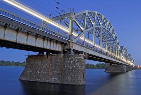 treno espresso: La notte treno espresso sul ponte del fiume Daugava.