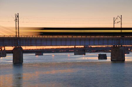 treno espresso: La mattina esprimere il treno sul ponte sul fiume Daugava.