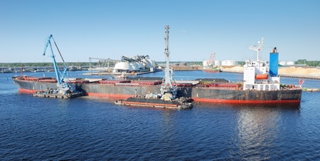 reloading: The cargo ship is loaded by coal in Riga port.