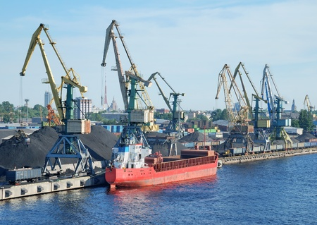 The cargo ship is loaded by coal in Riga port.